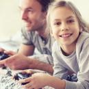 Девочка вместе с папой играет в компьютерные игры