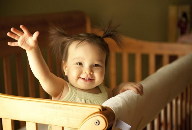 Маленькая девочка машет рукой из детской кроватки