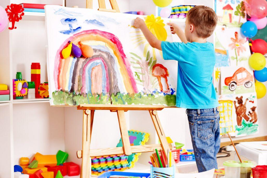 Мальчик рисует на мольберте