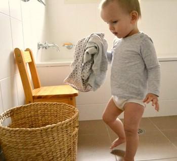 Ребёнок кладет вещи в корзину для грязного белья