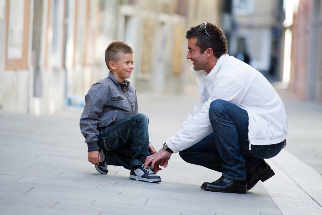 Папа завязывает сыну шнурки