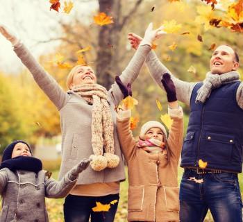 Счастливая семья бросает в воздух золотые листья
