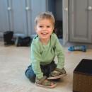 Счастливый ребёнок играет с обувью