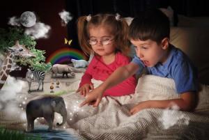 Маленькие мальчик и девочка представляют себе слона и других животных