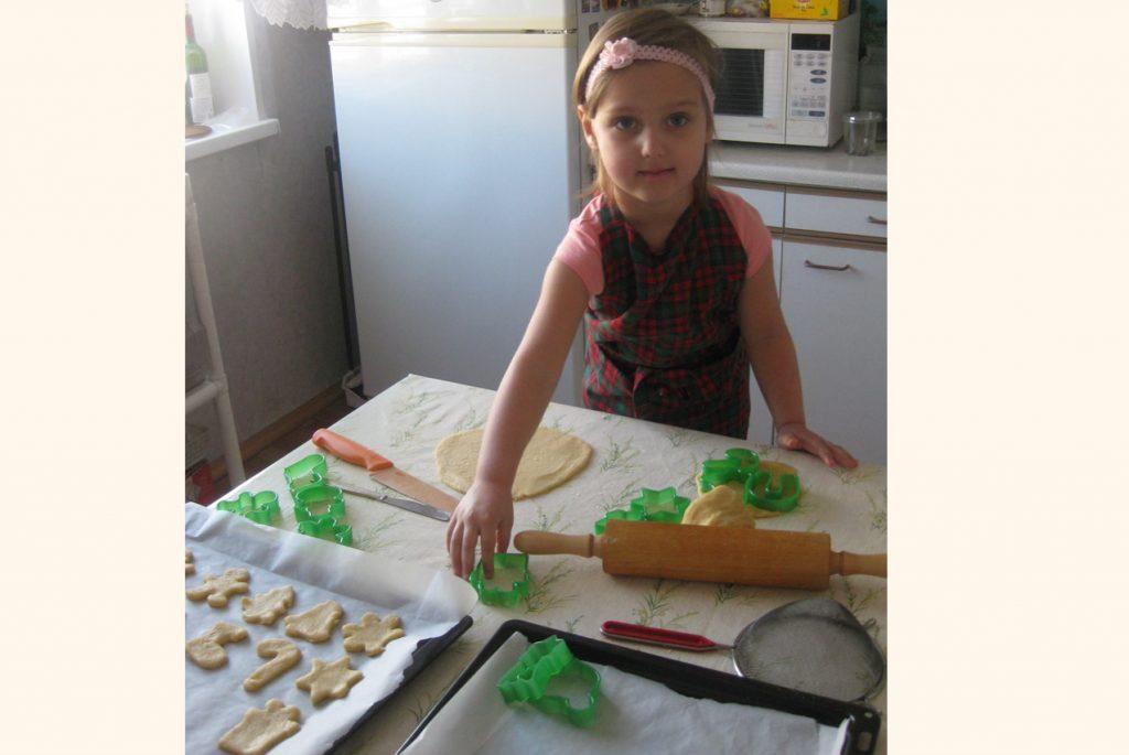 Девочка с помощью формочек вырезает новогоднее печенье из теста