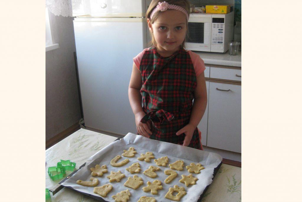 Девочка стоит рядом с противнем, на котором лежит новогоднее печенье