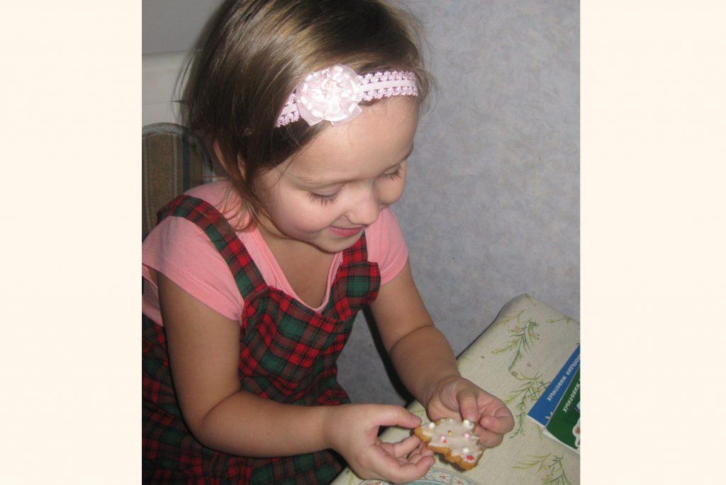 Девочка украшает новогоднее печенье