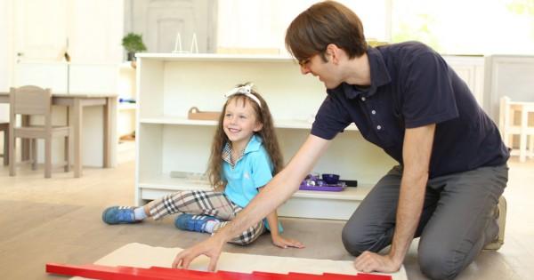 Педагог показывает ребенку Монтессори-материал красные штанги