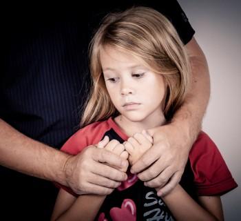 Грустная девочка, которую взрослый держит за руки, потому что родителю не важны интересы иебёнка