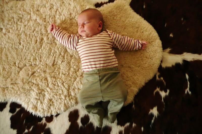 Новорождённый малыш спит на мягком ковре