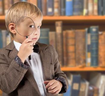 Мальчик с большой лупой в библиотеке