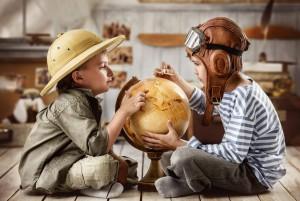 Двое детей играют в путешественников и изучают глобус