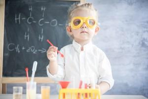 Девочка делает опыты в классе химии