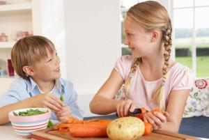 Мальчик и девочка вместе режут овощи