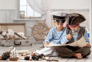 Двое мальчиков, играя в мореплавателей, изучают карту