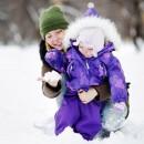 Мама гуляет с ребёнком рассматривают снег на ладони