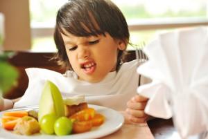 Мальчик кривится, глядя на тарелку с фруктами