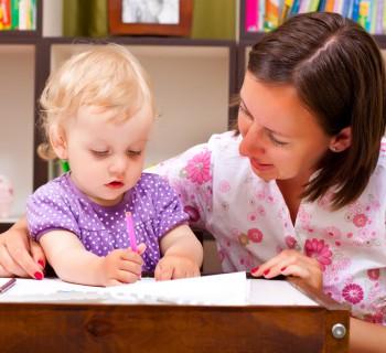 Мама учит маленькую девочку писать