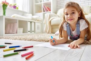Девочка лежит на полу и рисует цветными карандашами