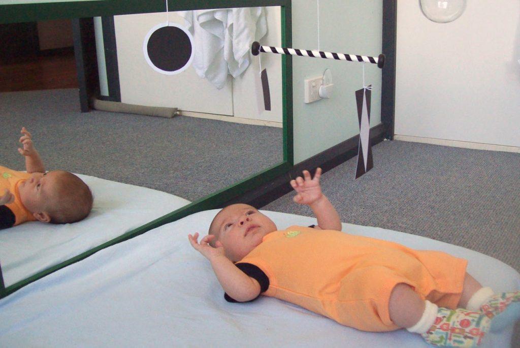 Ребёнок лежит и смотрит на Монтессори-мобиль