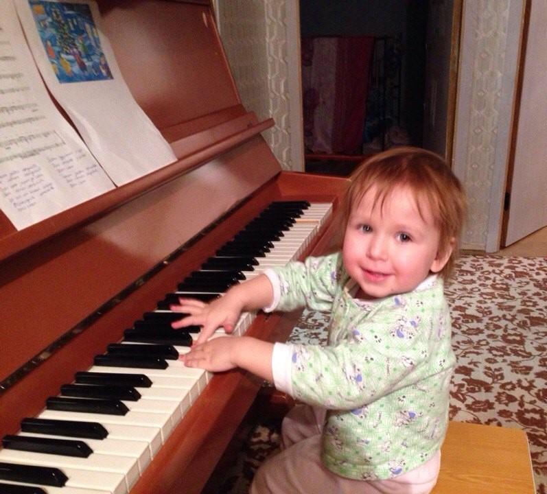 Маленькая девочка играет на пианино
