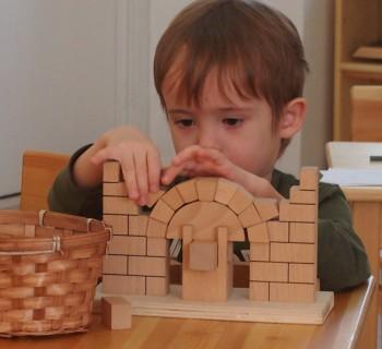Мальчик работает с Монтессори-материалом римская арка