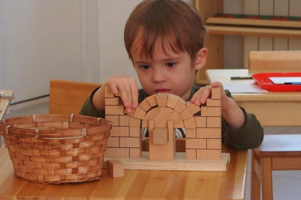 Увлеченная работа ребенка с Монтессори-материалом римская арка