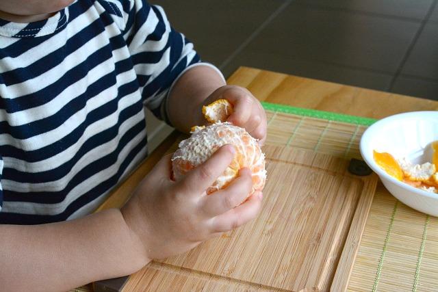 Ребенок чистит мандарин