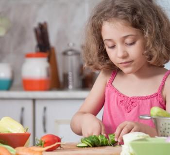 Девочка режет овощи на кухне