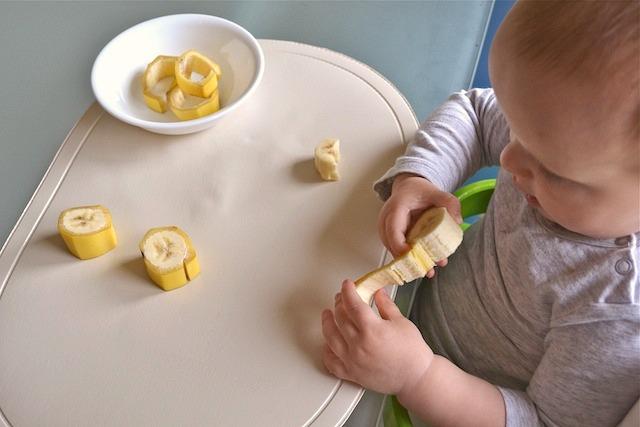 Маленький мальчик чистит банан