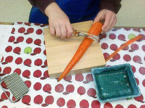 Девочка режет морковь