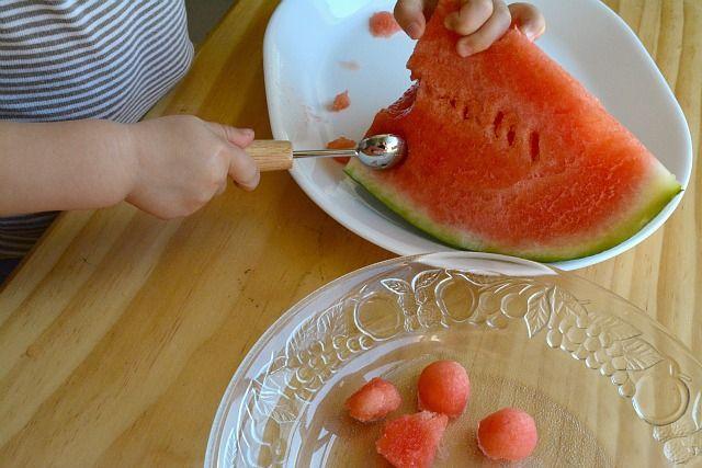 Ребенок чистит арбуз с помощью ложки