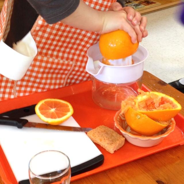 Ребенок выжимает сок из апельсинов