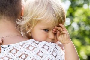 Ребенок плачет на плече у своей мамы