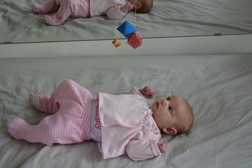 Младенец-девочка внимательно наблюдает за мобилем из октаэдров