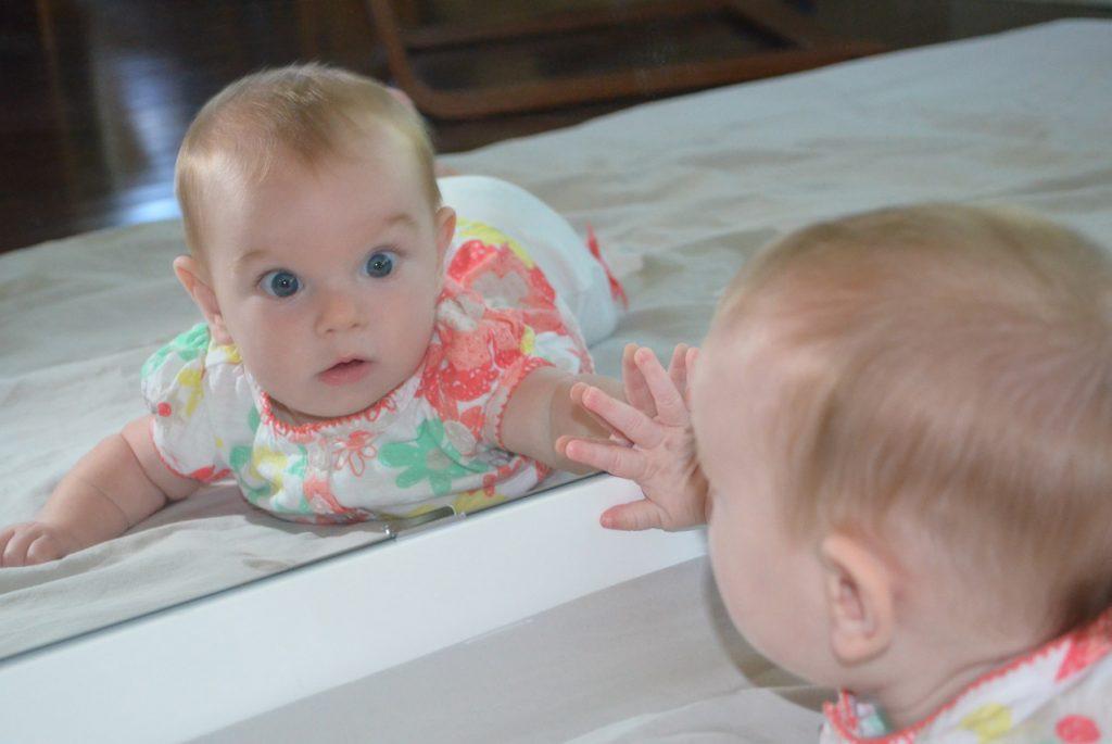 Младенец разглядывает свое отражение в зеркале