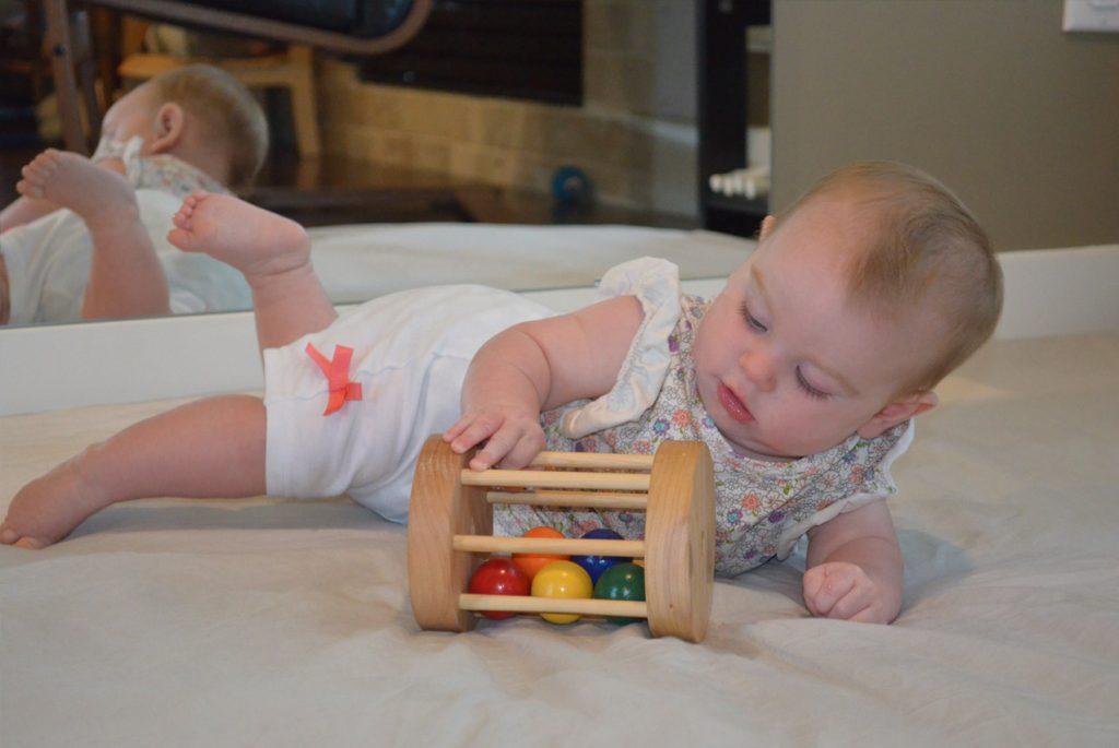 Малыш играет с деревянной игрушкой
