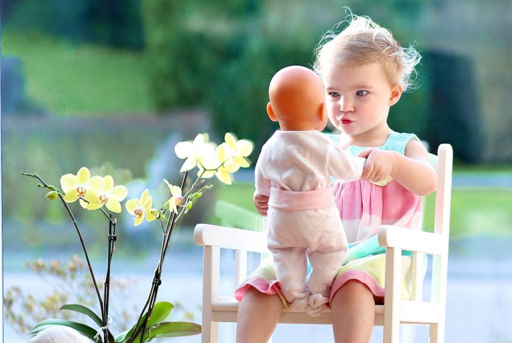 Маленькая девочка играет с куклой