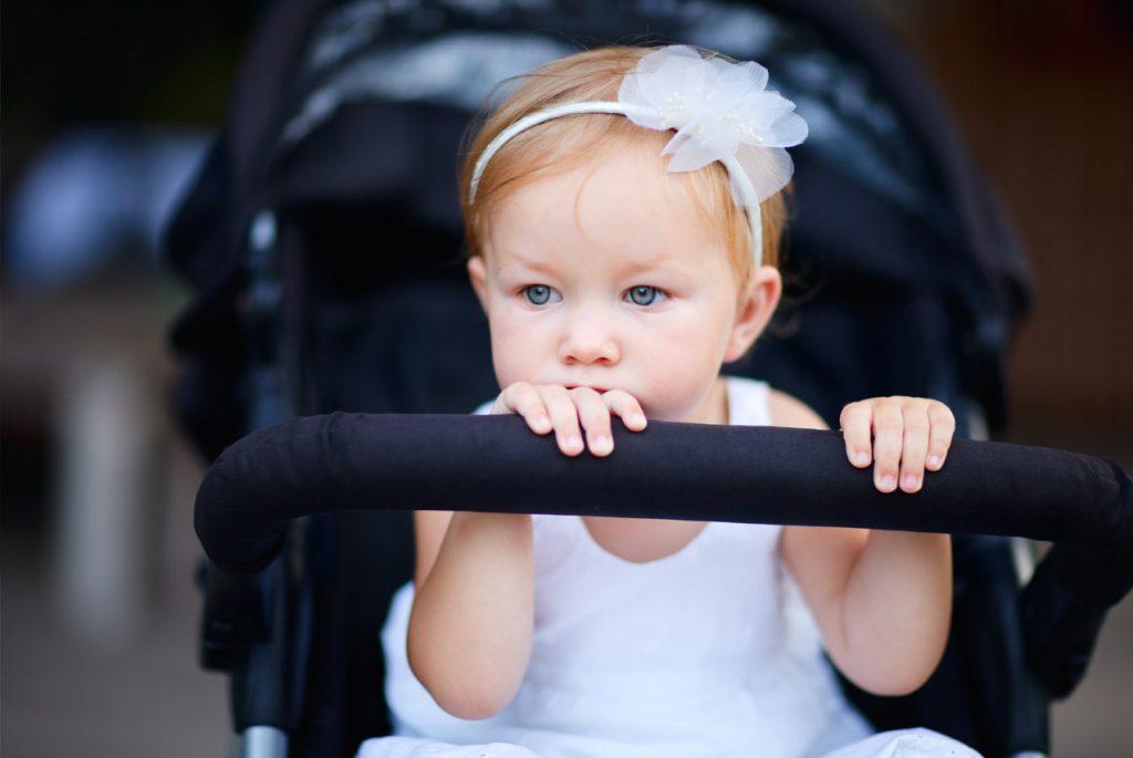 Маленькая грустная девочка сидит в коляске