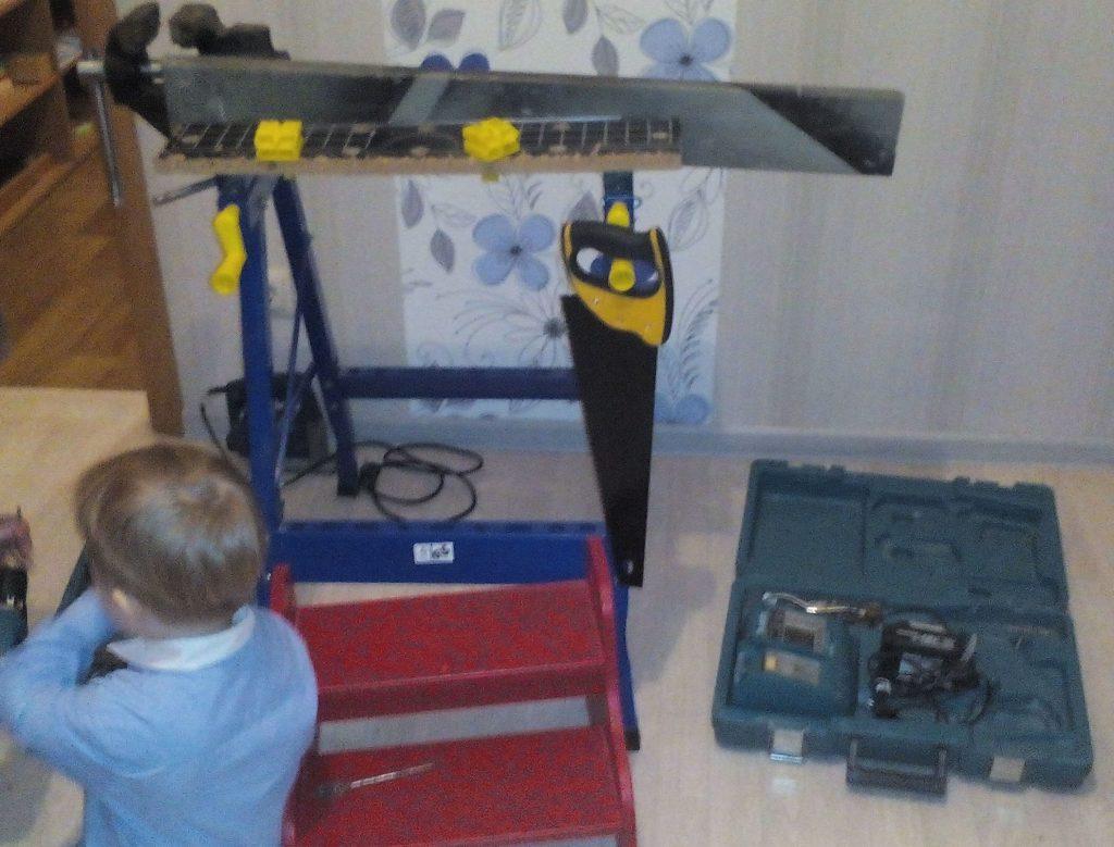 Ребенок с помощью инструментов мастерит что-то