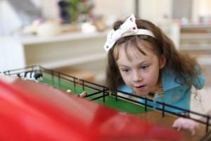 Монтессори-класс: девочка рассматривает игрушечную ферму