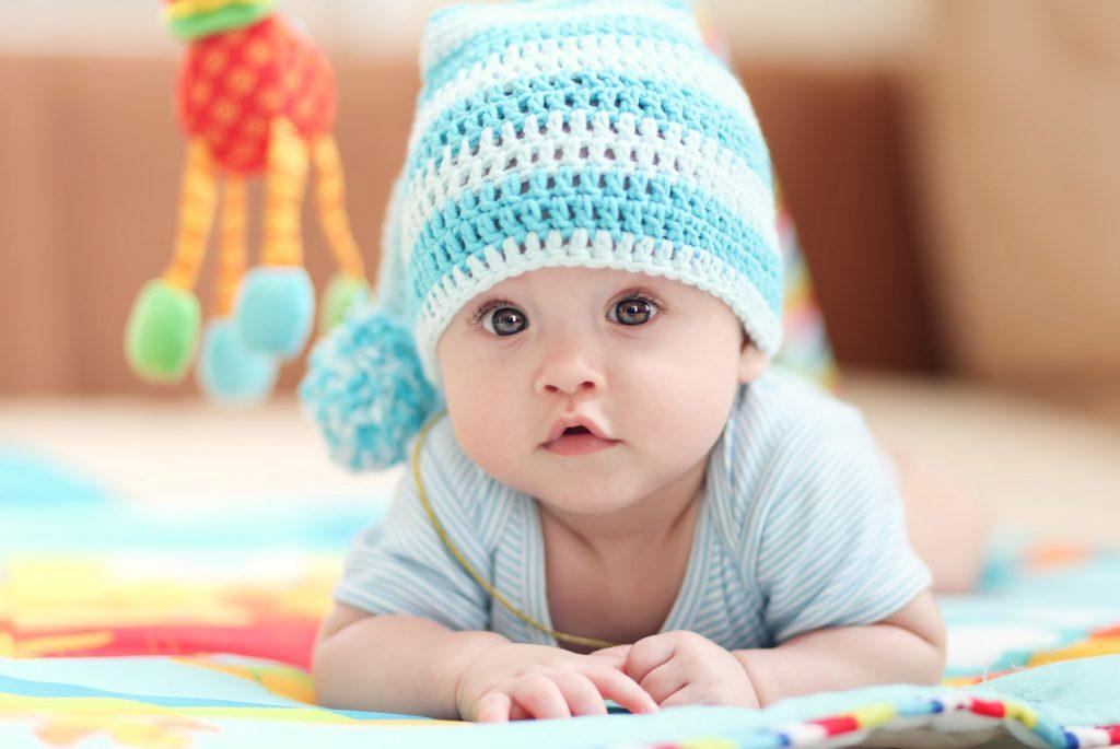 Маленький кареглазый ребёнок в шапочке лежит