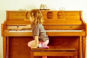 Маленькая девочка нажимает на клавиши пианино