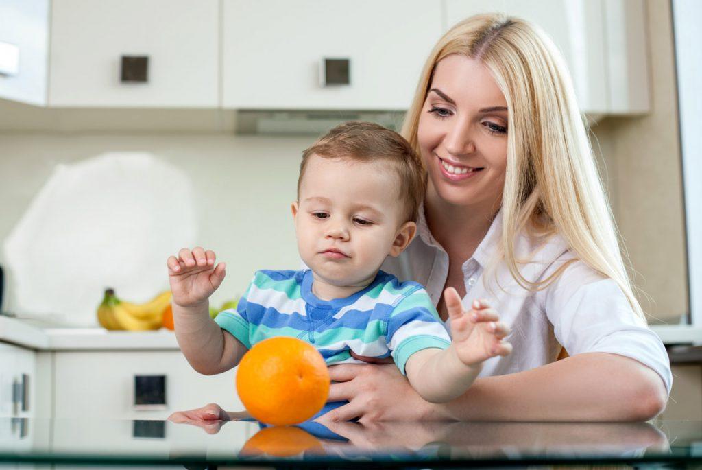 Мама и маленький мальчик смотрят на апельсин