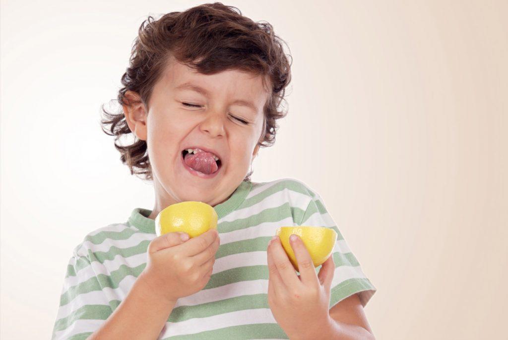 Мальчик пробует лимон и кривится