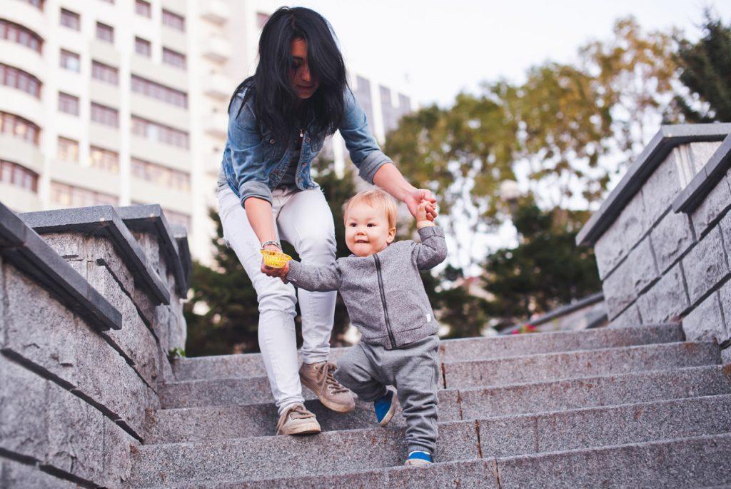 Активный малыш спускается по лестнице с помощью мамы