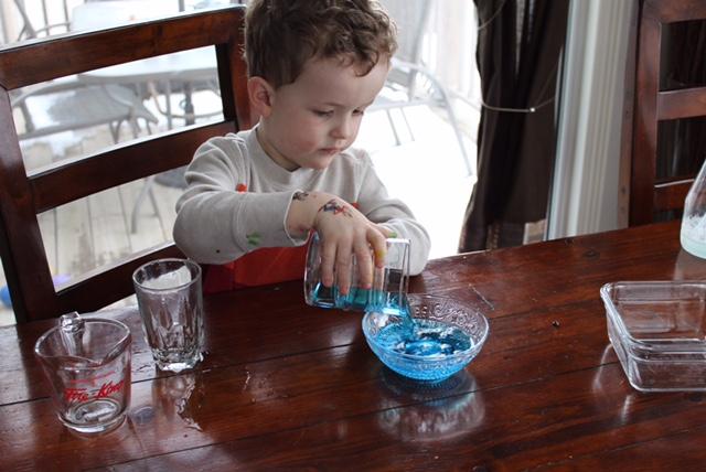 Ребёнок переливает воду из одной ёмкости в другую