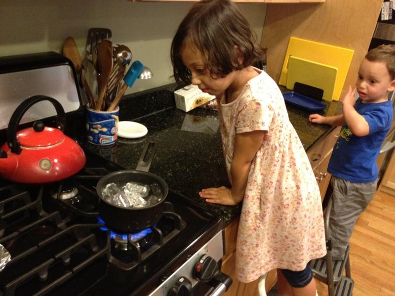 Мальчик и девочка на кухне растапливают лёд