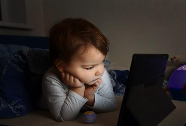 Мальчик смотрит мультики на планшете