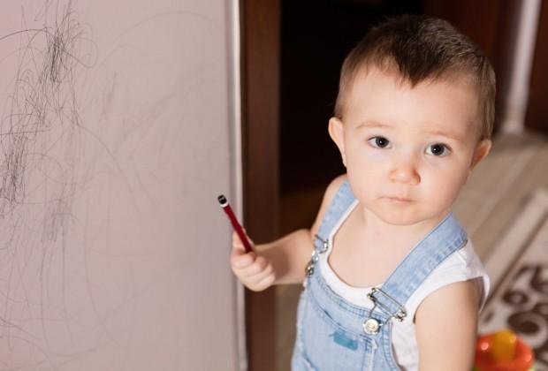 Мальчик рисует на стене